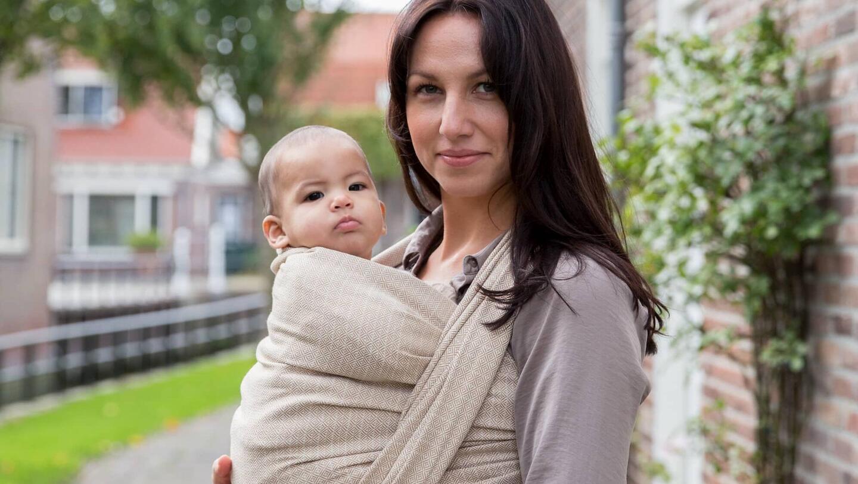 Mutter mit dunklen Haaren und Kind in beigem Babytragetuch