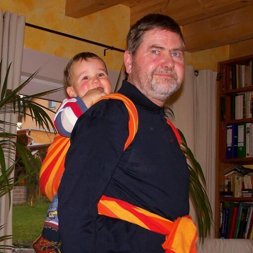 [Translate to Englisch:] Günter Schwartzer (Firmengründer von Storchenwiege) mit Baby in Babytragetuch