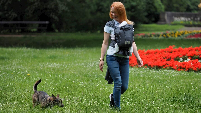 [Translate to Französisch:] Mutter mit WrapBabyCarrier spazierend auf Wiese mit Hund